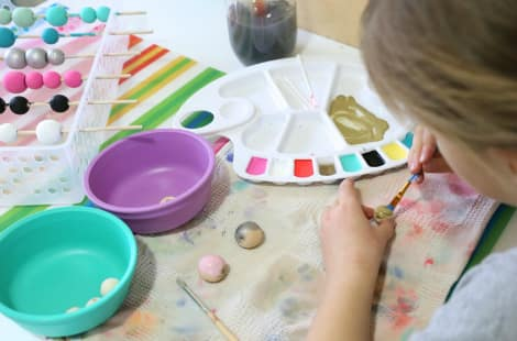 A little girl painting a bead gold with racks of beads drying in the background