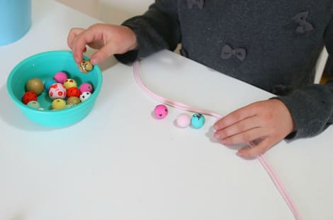 The bowl of painted and decorated beads sits beside a child as she picks which ones she wants to put on the fabric strip