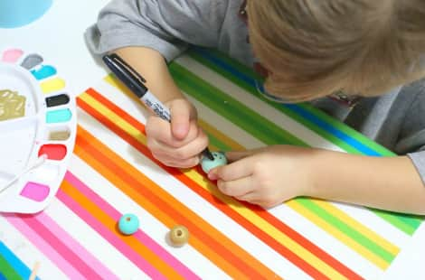 A child decorates a painted bead with a black permanent marker