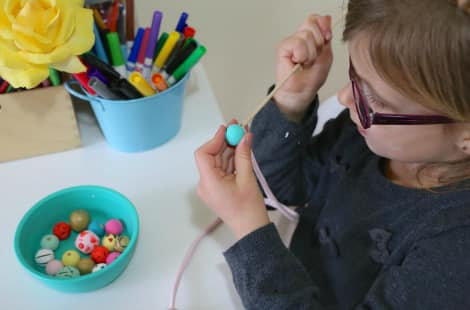A child using a wooden skewer to help push the fabric strip through a wooden bead