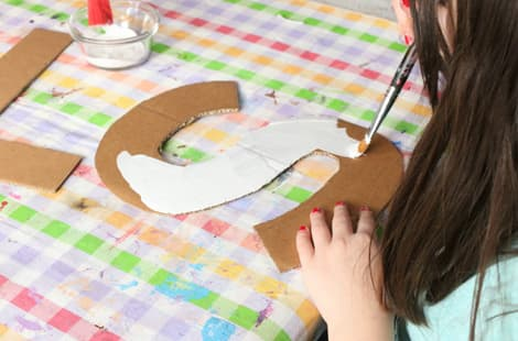 Little girl painting a cardboard