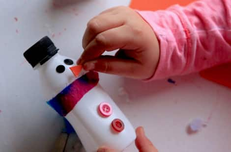 A child gluing the snowman's nose on