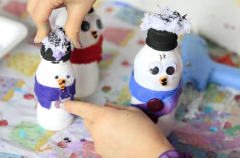 A child gluing yarn to the snowman's lid-hat