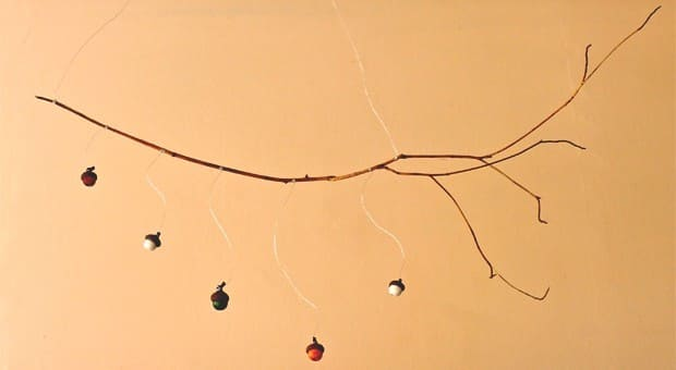 A mobile made with acorns and a branch.