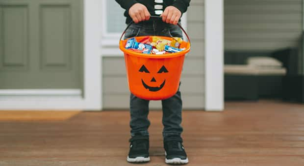 Child holds halloween jack-o-lantern full of candy
