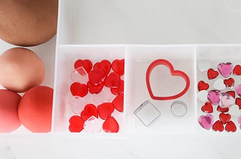 Play dough balls, jewels and cookie cutters in compartments.