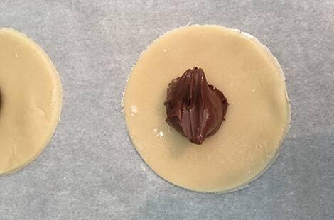 Adding chocolate hazelnut spread to cookie dough.