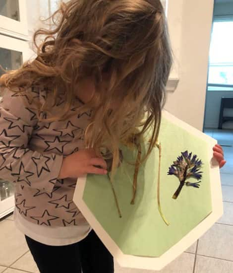 Child holds pressed flower picture.