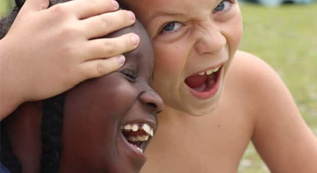 Black and white kids laugh together