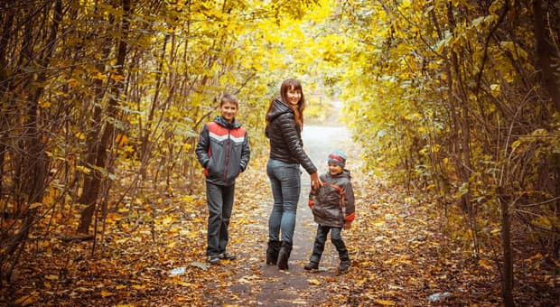 A happy woman walking in autumn woods with her children.