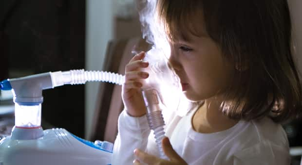 A child using a nebulizer for asthma