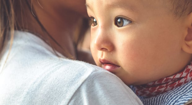 An Asian mother holds her child in a warm embrace