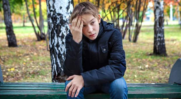 A young boy sits alone looking distraught