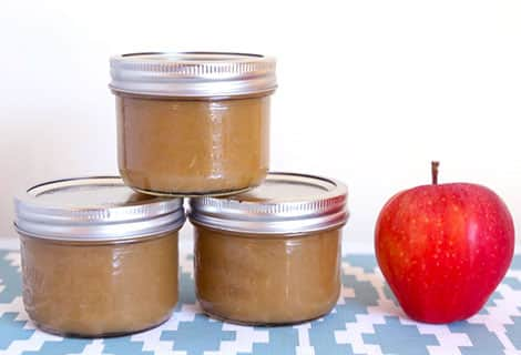 Three jars of slow-cooker applesauce next to a bright red apple.