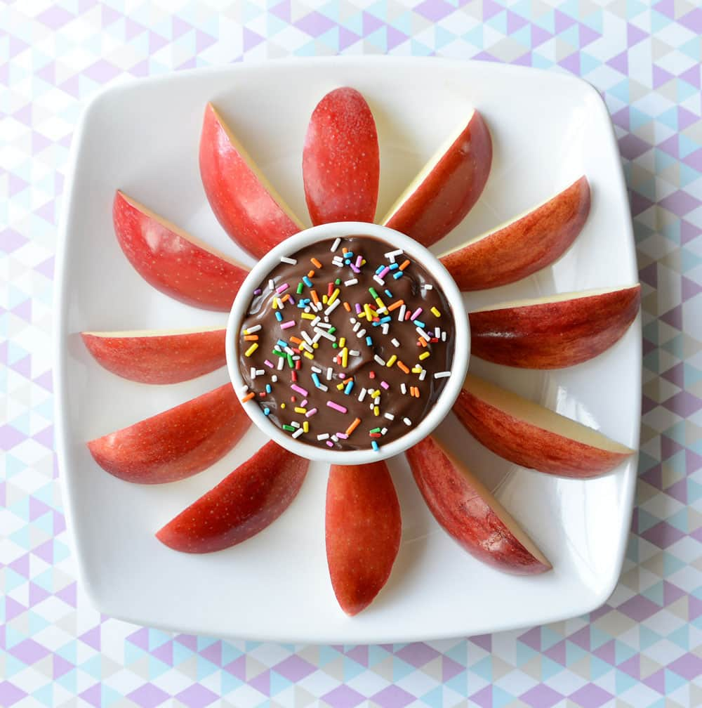 A small bowl of chocolate pudding and sprinkles surrounded by apple slices.