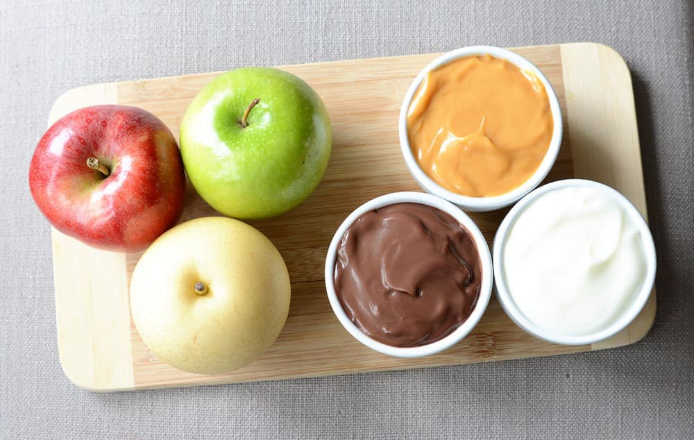 Three apples and three small bowls of dip: chocolate pudding, butterscotch pudding and yogurt.