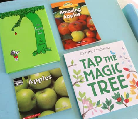 Four books about apples and seasons laid out for reading: The Giving Tree by Shel Silverstein; Amazing Apples from Scholastic; Apples by Welcome Books from Scholastic and Tap the Magic Tree by Christie Matheson.