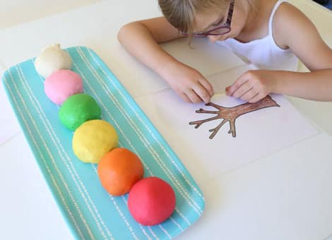 Adding white play-dough icicles to the tree trunk play dough mat.