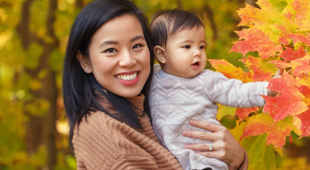 A chinese mother and daughter hang outside in a wooded area.