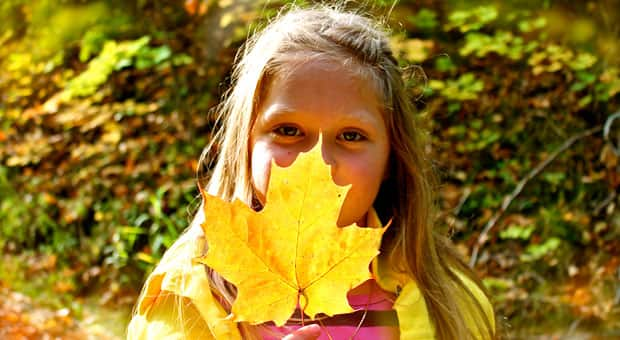 A girl holds a leaf in front of her face.