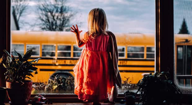 child looking tentatively at a yellow school bus