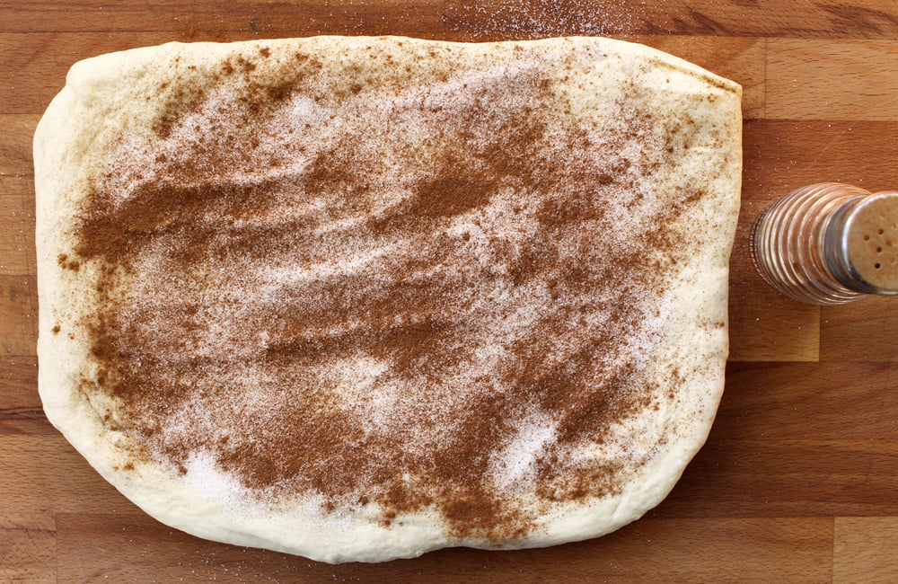 Bread dough sprinkled with cinnamon and sugar.