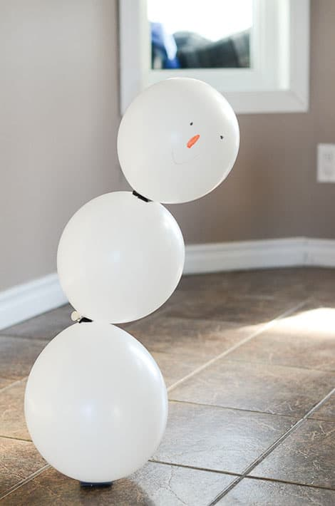 A lovely little lopsided balloon snowman, assembled. His face has been drawn on with permanent markers.