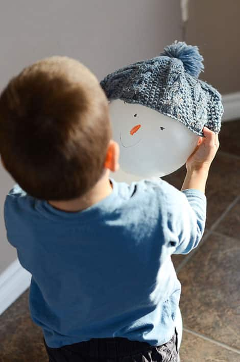 A boy putting a grey winter hat on the balloon snowman.