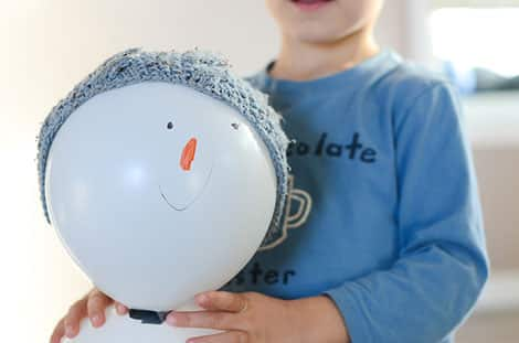 Boy standing and holding up his adorable balloon snowman with a winter hat and a face drawn on with permanent markers.