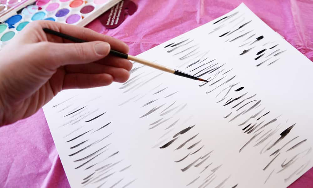 Small black stripes painted on white paper.