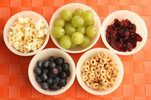 Bowls of popcorn, grapes, blueberries, dried fruit and