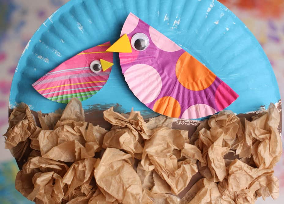 Finished craft: two colourful liners folded in half and made to look like little birdies with googly eyes and foam beaks glued on. They birds are glued onto a paper plate, the top half of which is painted blue, and the bottom half is covered in crumpled brown paper.