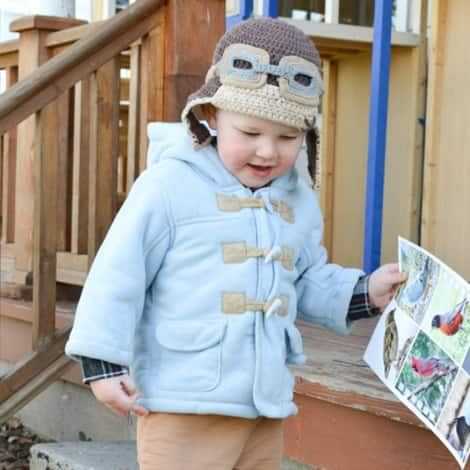 A young boy walks outside and carries a bird identification sheet.
