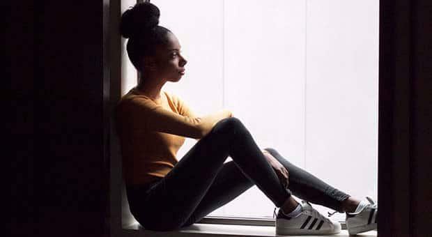 Black teen sits in window sill.