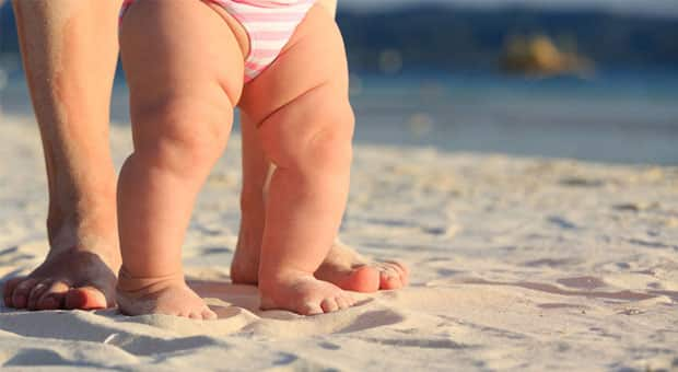 A mom and her baby on the beach.