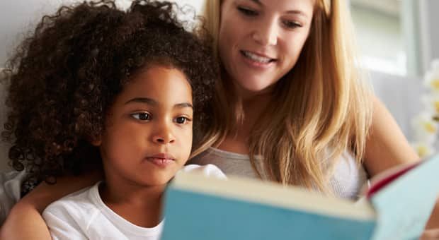 A mother and daughter reading in bed.