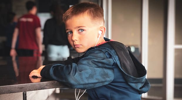 young boy with ear buds looks at camera
