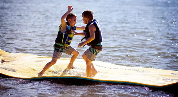 Boys playing on float mat on lake