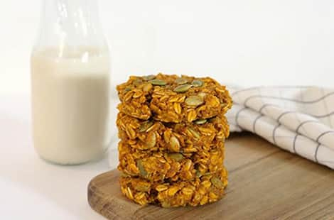 Breakfast cookies piled up beside a glass of milk.