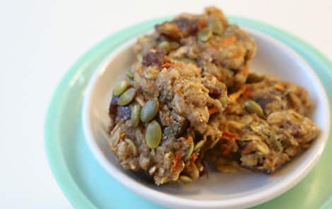 A plate of breakfast cookies with pumpkin seeds, raisins and grated carrot.