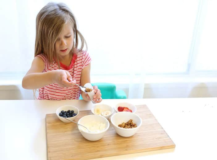 A little girl filling the popsicle moulds with granola, fruit and yogurt.