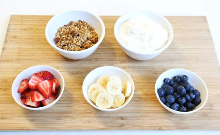 Bowls of ingredients ready for assembly—granola, strawberries, bananas, blueberries and yogurt.