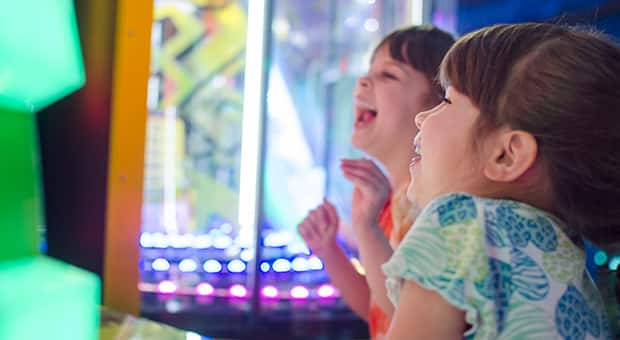 Two little girls look at arcade