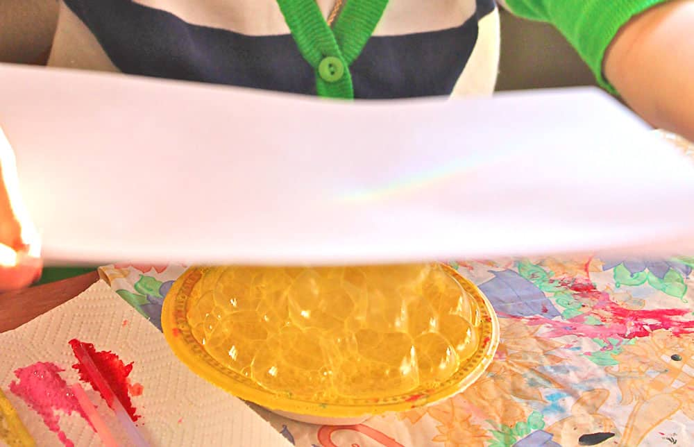 Lowering a piece of paper over a bowl mounded with yellow bubbles.