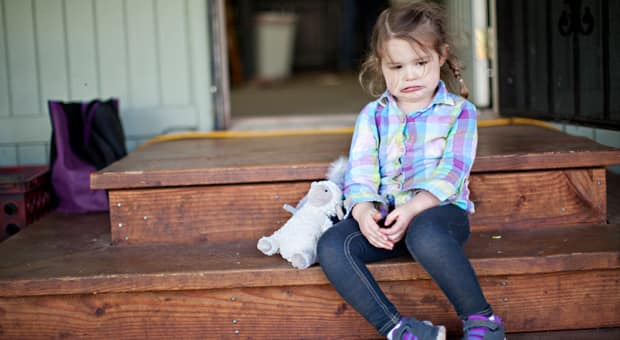 a young girl sits upset after school with her backpack thrown to the side