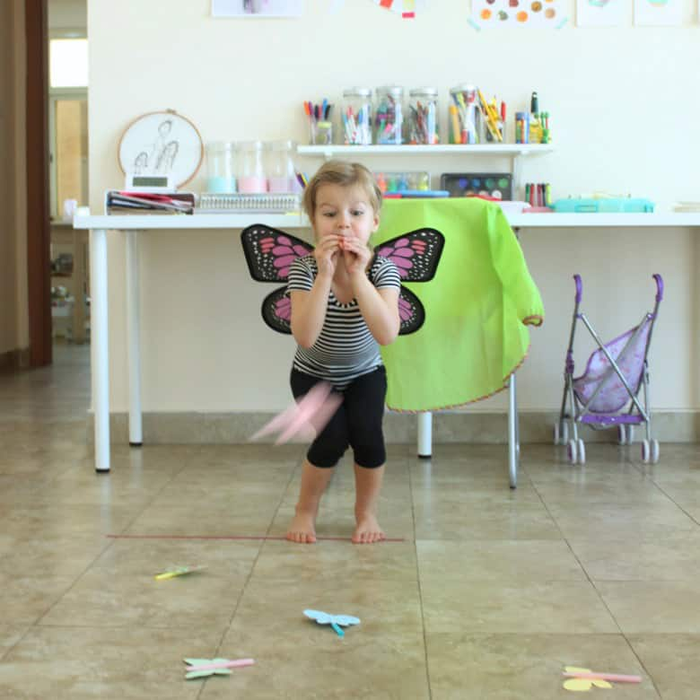A girl dressed as a butterfly launches a butterfly blower across the room.