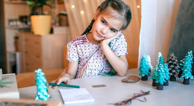 a young girl proudly sits in front of her handmade christmas ornament which she plans to send as gifts