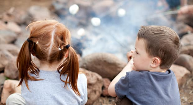 two children roasting marshmallows over a campfire
