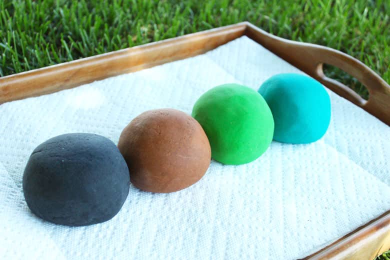 Homemade play dough in four colours: black, brown, green and blue.
