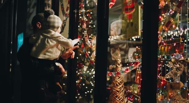 a father and daughter window shop at a holiday display